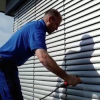 Gebäudereiniger spruht reinigungsmitttel auf JAlousien https://fensterputzerlauf.de/jalousienreinigung Eckental